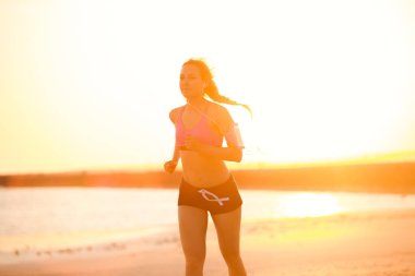 silhouette of sportswoman in earphones with smartphone in running armband case jogging on beach against sunlight