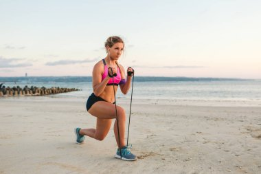 sportswoman in earphones with smartphone in armband case doing exercise with stretching band on beach