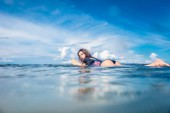 Fotografie boční pohled mladé sportovkyně v neopren na desce surfing v oceánu na Nusa dua Beach, Bali, Indonésie