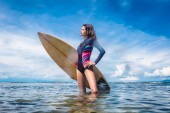 Photo side view of attractive sportswoman in wetsuit with surfing board standing in ocean at Nusa dua Beach, Bali, Indonesia