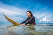 Photo portrait of young sportswoman in wetsuit on surfing board in ocean at Nusa dua Beach, Bali, Indonesia