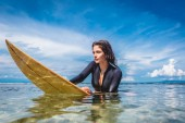 young sportswoman in wetsuit on surfing board in ocean at Nusa dua Beach, Bali, Indonesia