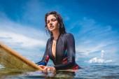 Fotografie portrait of sportswoman in wetsuit on surfing board in ocean at Nusa dua Beach, Bali, Indonesia