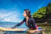 Photo side view of pretty sportswoman in wetsuit on surfing board in ocean at Nusa dua Beach, Bali, Indonesia
