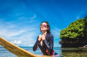 Photo sportswoman in wetsuit and sunglasses on surfing board in ocean at Nusa dua Beach, Bali, Indonesia