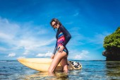 Photo attractive young woman in wetsuit and sunglasses with surfboard posing in ocean at Nusa dua Beach, Bali, Indonesia