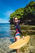 Fotografie krásná mladá žena v obleku a sluneční brýle s Surf pózuje v oceánu na Nusa dua Beach, Bali, Indonésie