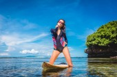 Photo attractive woman in wetsuit and sunglasses with surfboard posing in ocean at Nusa dua Beach, Bali, Indonesia