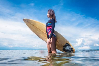 side view of attractive sportswoman in wetsuit with surfing board standing in ocean at Nusa dua Beach, Bali, Indonesia
