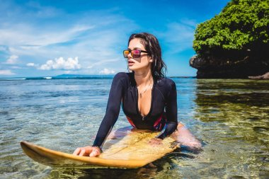 sportswoman in wetsuit and sunglasses on surfing board in ocean at Nusa dua Beach, Bali, Indonesia