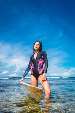 attractive young woman in wetsuit with surfboard posing in ocean at Nusa dua Beach, Bali, Indonesia