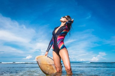 attractive young woman in wetsuit and sunglasses with surfboard posing in ocean at Nusa dua Beach, Bali, Indonesia
