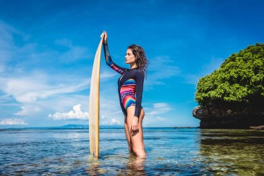 side view of pretty woman in wetsuit with surfboard posing in ocean at Nusa dua Beach, Bali, Indonesia