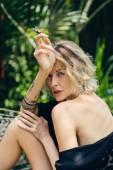 Fotografie blonde Frau in schwarzer Kleidung mit Zigarette in der hand ruht auf Bank auf Terrasse
