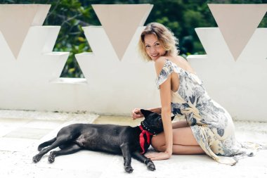 blond woman in dress resting on terrace together with dog