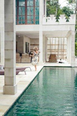back view of woman in beautiful dress running near swimming pool at villa