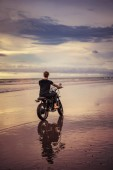 back view of biker with motorbike on ocean beach with cloudy weather