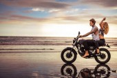 Photo side view of couple riding motorcycle on ocean beach
