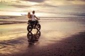 girlfriend with open arms sitting on motorcycle after boyfriend on ocean beach