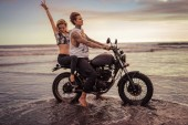 Fotografie girlfriend showing peace sing during riding motorcycle on ocean beach