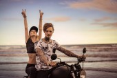 girlfriend sitting on motorcycle and showing peace sing on ocean beach