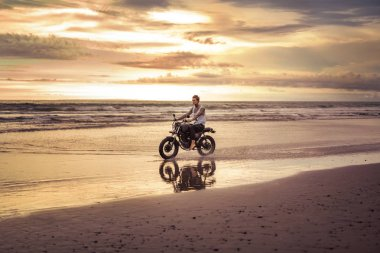 tattooed biker riding motorcycle on ocean beach during sunset