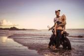 Photo stylish boyfriend hugging girlfriend near motorcycle on ocean beach