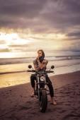 zamyšlený hezký potetovaný motorkář sedí na motorce na pláži u oceánu