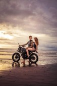 boyfriend and girlfriend sitting on motorcycle at sandy beach