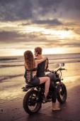 Fotografie Rückansicht des Freund und Freundin sitzen auf Motorrad am Strand bei Sonnenaufgang