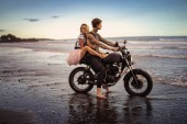 Photo side view of couple hugging on motorcycle on ocean beach