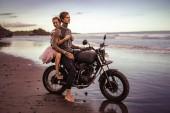 Fotografie smiling girlfriend hugging boyfriend on motorcycle on ocean beach