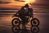 Fotografie sexy couple hugging on motorbike at beach during sunset