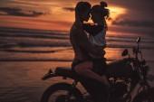 Fotografie shirtless boyfriend hugging girlfriend on motorcycle at beach during sunset