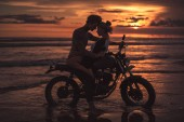 Fotografie passionate couple hugging and touching with foreheads on motorcycle at beach during sunset