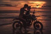 Fotografie leidenschaftliche Paare umarmen und berühren mit der Stirn auf Motorrad am Strand bei Sonnenuntergang