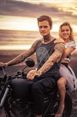 young heterosexual couple sitting on motorcycle and looking at camera at beach