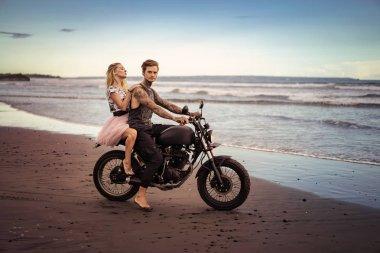 couple sitting on motorbike on seashore during beautiful sunrise