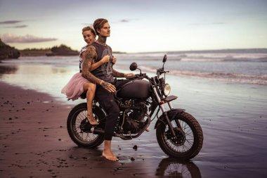 Smiling girlfriend hugging boyfriend on motorcycle on ocean beach stock vector