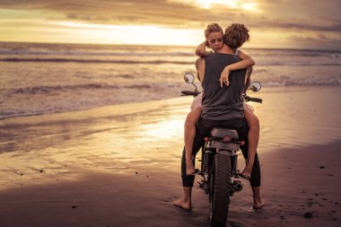 heterosexual couple hugging on motorcycle on ocean beach during beautiful sunrise