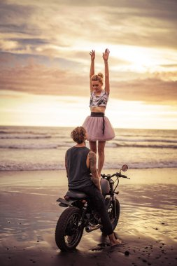 happy girlfriend standing on motorcycle with hands up on ocean beach