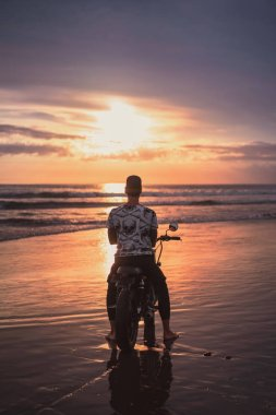 back view of man sitting on motorbike on ocean beach and looking at beautiful sunset