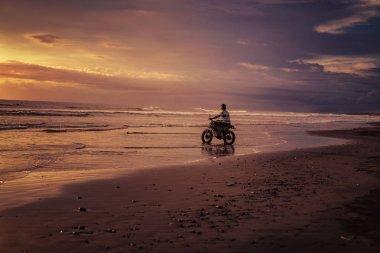 man riding motorbike into ocean during sunrise