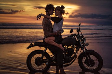 passionate couple cuddling on motorcycle at beach during sunset