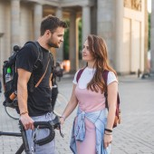 couple of tourists with backpacks looking at each other at Pariser Platz, Berlin, Germany