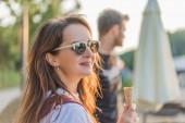 Detailní záběr portrét mladé ženy v sluneční brýle se zmrzlinou