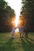 pár s batohy a kolo stojí na louce s zapadajícího slunce za