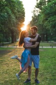 young man holding happy girlfriend with closed eyes in park with setting sun behind
