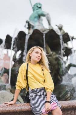 young woman looking away in front of Neptunbrunne in Berlin, Germany