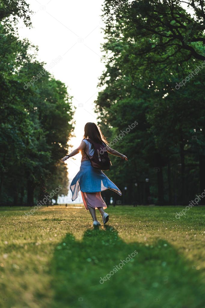 rear view of young woman with wide arms having fun in park